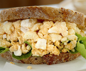 Smashed egg sandwich filled dark background